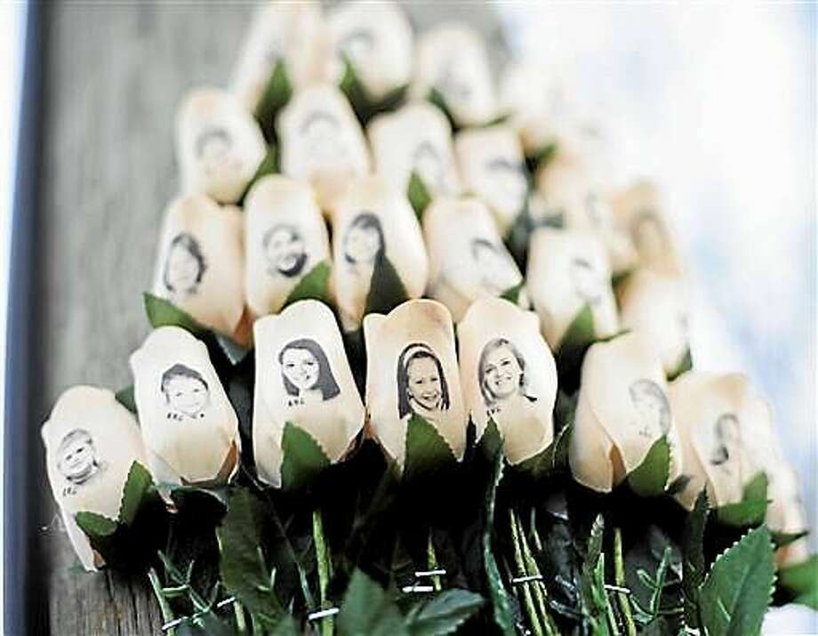 In this Jan. 14, 2013 file photo, white roses with the faces of victims of the Sandy Hook Elementary School shooting are attached to a telephone pole near the school on the one-month anniversary of the shooting. Photo: Associated Press   / FR125654 AP