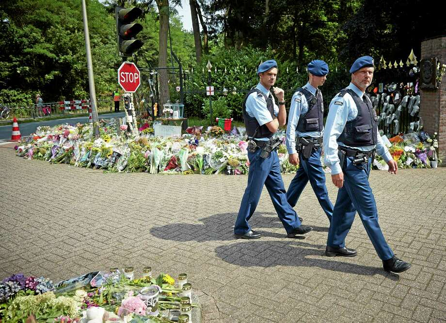 Military police officers walk past flowers placed at the entrance of a military barracks where forensic experts are working to identify bodies and human remains recovered from the wreckage of Flight 17, in the central city of Hilversum, Netherlands, Thursday, July 31, 2014. (AP Photo/Phil Nijhuis) Photo: AP / AP