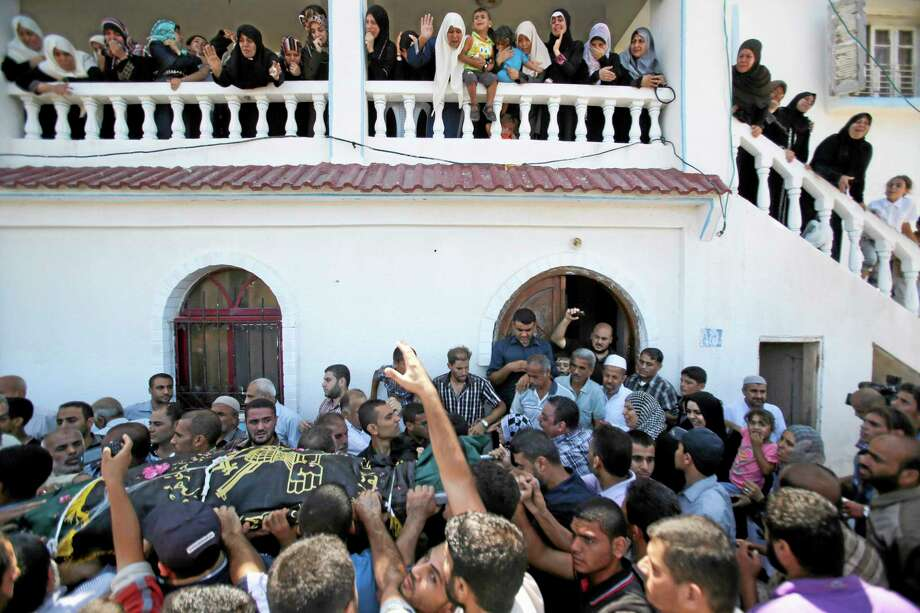 Palestinians carry the body of Islamic Jihad militant Shaaban Al-Dahdouh, which was found under the rubble yesterday, during funeral in Gaza City, Wednesday, Aug. 6, 2014. (AP Photo/Hatem Moussa) Photo: AP / AP