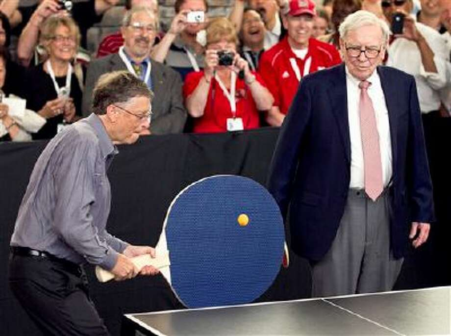 """FILE - In this May 6, 2012 file photo, Warren Buffett, chairman and CEO of Berkshire Hathaway, right, watches Bill Gates use an oversize paddle as they play doubles against table tennis prodigy Ariel Hsing in Omaha, Neb. Members of the economic elite are looking for ways to reduce the nation's growing income inequality for a variety of reasons, from self-interest to pangs of conscience. Buffet advocated for a progressive estate tax before members of Congress, saying in 2007, """"Dynastic wealth, the enemy of a meritocracy, is on the rise. Equality of opportunity has been on the decline. A progressive and meaningful estate tax is needed to curb the movement of a democracy toward plutocracy."""" (AP Photo/Nati Harnik, File) Photo: AP / AP"""