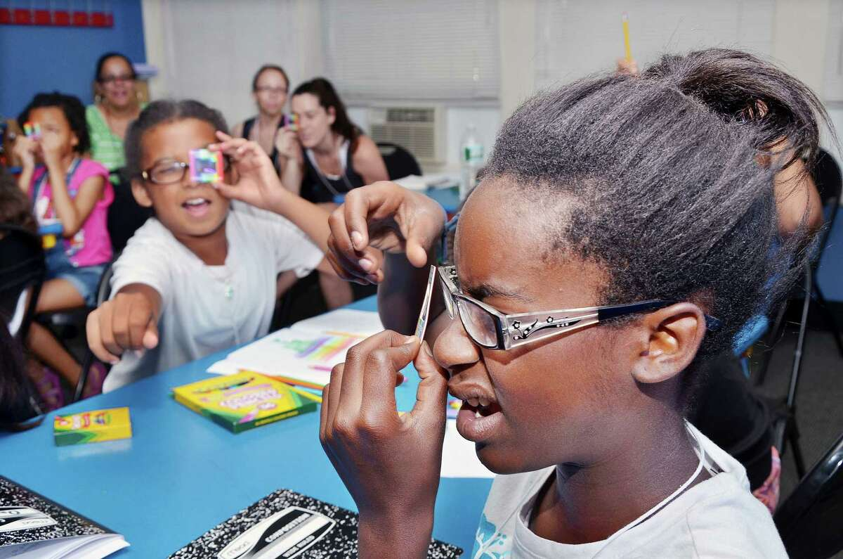 Catherine Avalone - The Middletown Press Tyshala Morris-Hayes, 11, at right and Julia Martinez, 10, react to using a linear diffraction grating to see scattered red laser light during a class taught by Wesleyan University physics professor Christina Othon at the Girls in Science Summer Camp at Green Street Arts Center in Middletown. Wesleyan faculty and students taught 10 girls about mutations, light, color, DNA, gardens, insects, created germ plates, and designed a bacteria in the art room throughout the week.