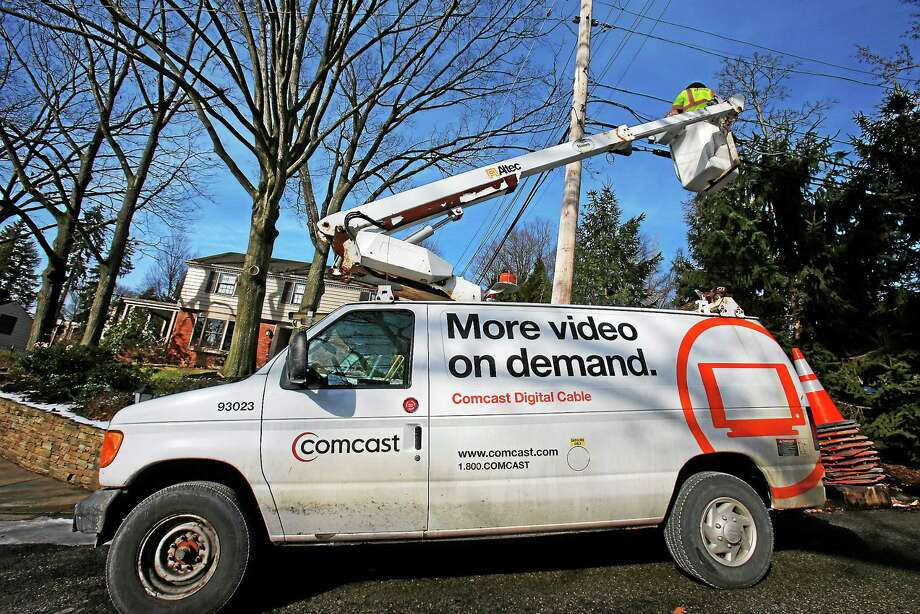 A Comcast cable truck is pictured working in front of a home. Photo: AP Photo/Gene J. Puskar  / AP