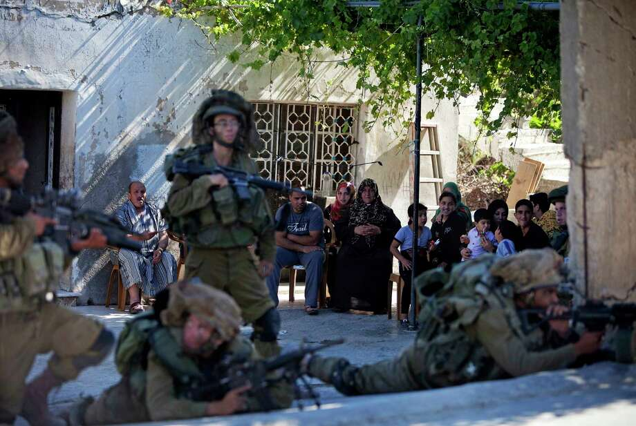 A Palestinian family look at Israeli soldiers during a military operation searching for three missing teenagers, near the West Bank city of Hebron, June 15 Photo: AP Photo  / AP