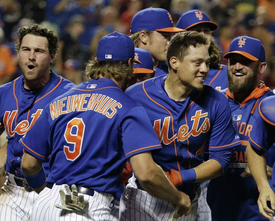 The Mets' Wilmer Flores, center right, is mobbed by teammates after hitting a walk-off solo home run in the 12th inning to defeat the Washington Nationals 2-1 Friday. Photo: Julie Jacobson  — The Associated Press  / AP