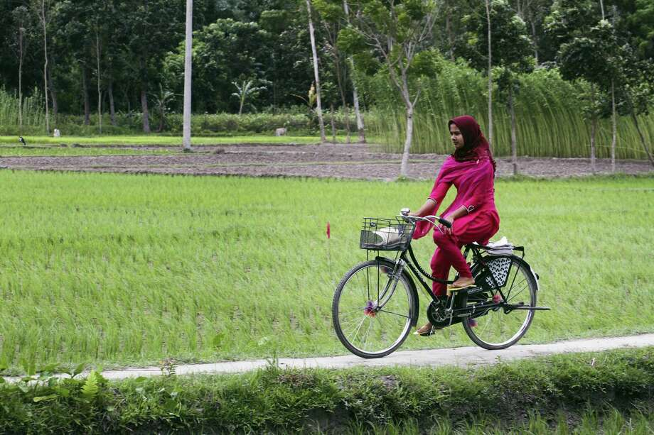 A girl rides a cycle after Bangladesh and India officially exchanged the adversely possessed enclaves at Dashiarchhara in in Kurigram district, 240 kilometers (150 miles) north of Dhaka, Bangladesh's capital, Saturday. Tens of thousands of stateless people who were stranded for decades along the poorly defined border between India and Bangladesh can finally choose their citizenship, as the two countries swapped more than 150 pockets of land at the stroke of midnight Friday to settle the demarcation line dividing them. Photo: AP Photo/Zakir Hossain Chowdhury / AP