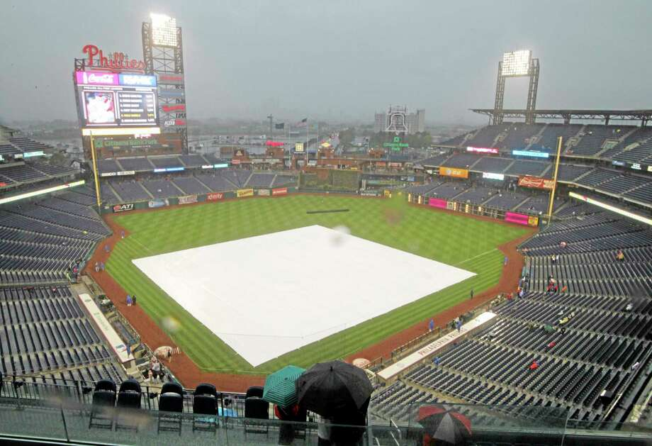 A tarp covers the infield as rain delays the start of Tuesday night's game between the New York Mets and the Phillies in Philadelphia. Wednesday's game has been canceled. Photo: H. Rumph Jr. — The Associated Press  / FR61717 AP