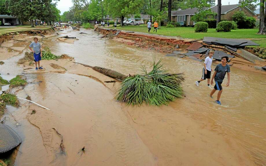 Stephen Halstead, left, Chris Halstead, middle, and Evan Dominguez, right, walk past an uprooted palm tree lying in a flooded section of  Piedmont Street after flood-water damage caused by torrential rains in Pensacola, Fla., Wednesday, April 30, 2014. (AP Photo/G.M. Andrews) Photo: AP / FR35697 AP