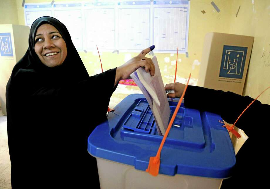 An Iraqi woman casts her vote inside a polling station for parliamentary elections in Baghdad, Iraq, Wednesday, April 30, 2014. Iraq is holding its third parliamentary elections since the U.S.-led invasion that toppled dictator Saddam Hussein.  More than 22 million voters are eligible to cast their ballots to choose 328 lawmakers out of more than 9,000 candidates. (AP Photo/Karim Kadim) Photo: AP / AP