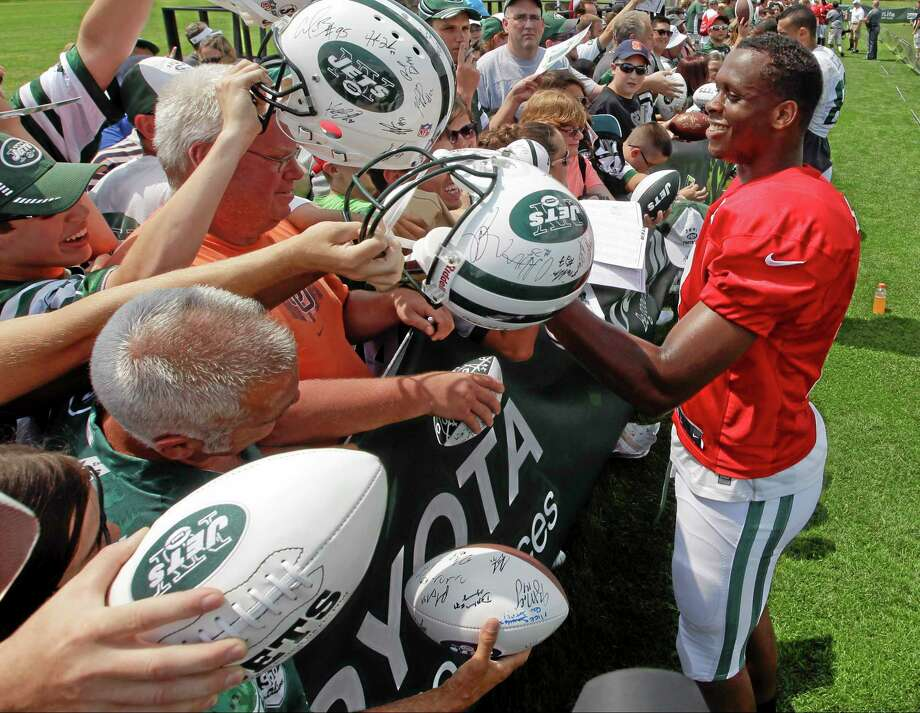 New York Jets quarterback Geno Smith signs autographs for fans after practice during an NFL football training camp on Saturday, July 26, 2014, in Cortland, N.Y.  (AP Photo/Frank Franklin II) Photo: AP / AP