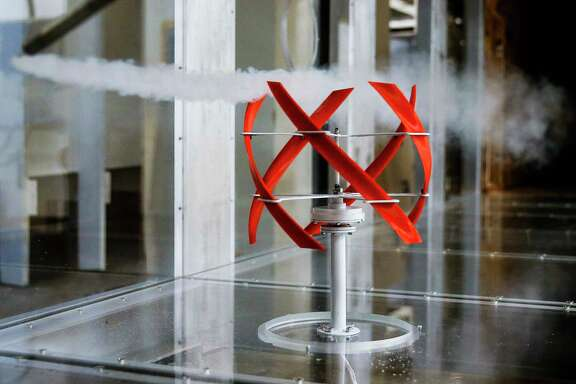 A stream of smoke in a wind tunnel flows past a 3D printed, helical shaped wind turbine model designed at the University of Houston Friday, Aug. 11, 2017 in Houston.  ( Michael Ciaglo / Houston Chronicle )