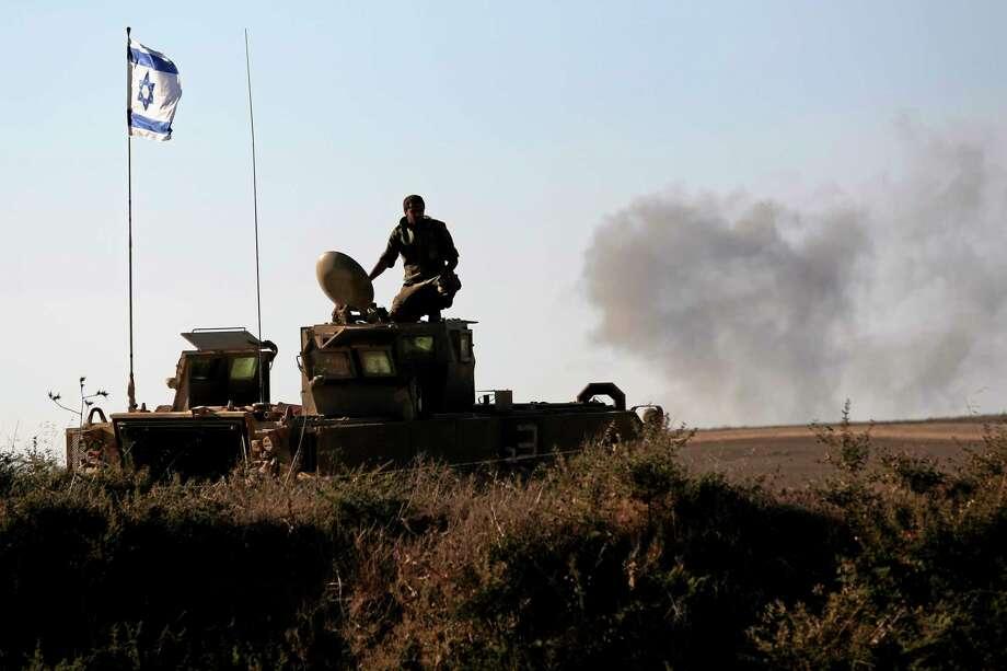 An Israeli solder looks on the site near the Israeli Gaza border, where a man was injured from a mortar shell fired from the Gaza Strip, Sunday, Aug. 3, 2014. (AP Photo/Tsafrir Abayov) Photo: AP / AP