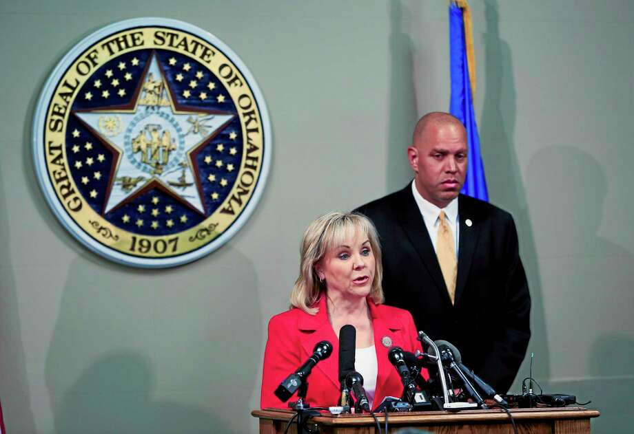 Oklahoma Gov. Mary Fallin, front, issues a statement to the media on the Execution of Clayton Lockett as Oklahoma Secretary of Safety and Security Michael C. Thompson, back, listens from the Oklahoma State Capitol in Oklahoma City on Wednesday, April 30, 2014. Lockett apparently died of a massive heart attack during his botched execution. (AP Photo/Alonzo Adams) Photo: AP / FR159426 AP