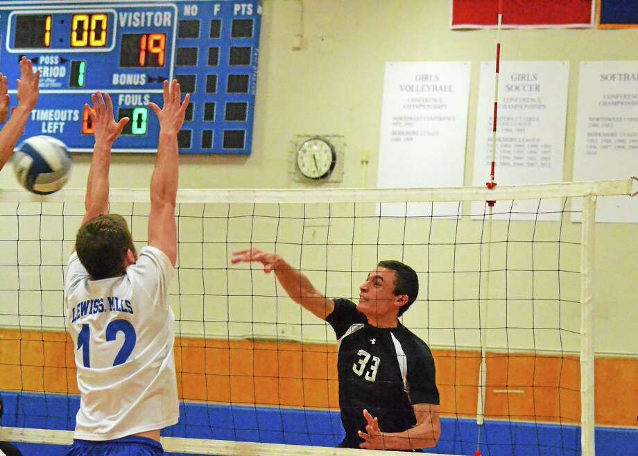 Xavier's Andre Zumerchik spiked the ball past Lewis Mills' Seth Ouellette. Zumerchik finished the match with 19 kills in the Falcons' 3-1 win over Lewis Mills. Photo: Pete Paguaga — Register Citizen