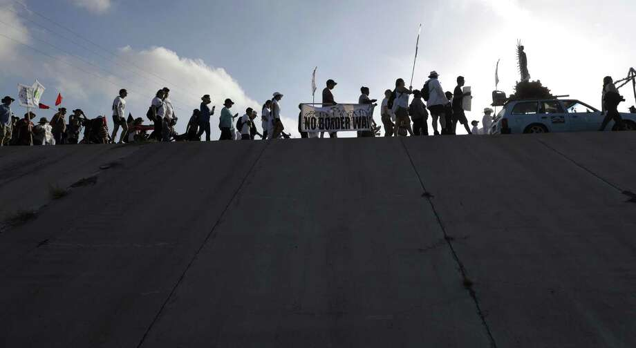 Hundreds of people march along a levee in South Texas toward the Rio Grande to oppose the wall the U.S. government wants to build on the river separating Texas and Mexico, Saturday, Aug. 12, 2017, in Mission, Texas. The area would be the target of new barrier construction under the Trump administration's current plan. (AP Photo/Eric Gay) Photo: Eric Gay / Associated Press / Copyright 2017 The Associated Press. All rights reserved.