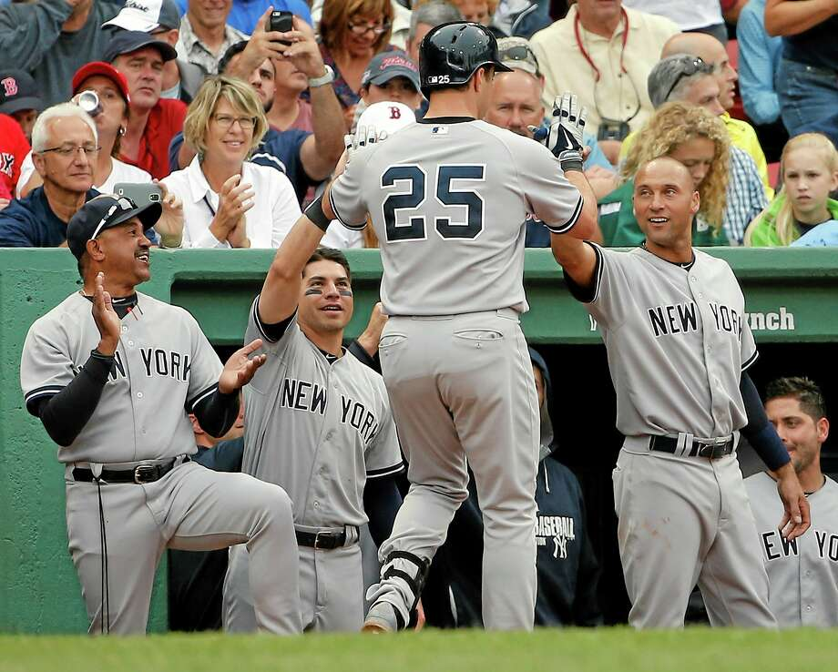 The Yankees' Mark Teixeira (25) is greeted by teammates after his home run in the fifth inning Saturday at Fenway Park. Photo: Winslow Townson — The Associated Press  / FR170221 AP