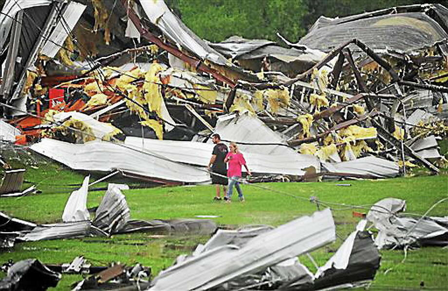 A man and woman examine the twisted wreckage of Glass Masters on U.S. 49 Frontage Road in Richland,  Miss., shortly after it was destroyed by a tornado late Monday afternoon, April 28, 2014.   With parts of the U.S. recovering from deadly tornadoes, more heavy storms are making their way across the South.  (AP Photo/The Clarion-Ledger, Joe Ellis) Photo: AP / The Clarion-Ledger