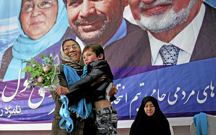 In this photo taken on Monday, March 17, 2014, Afghan vice presidential candidate, Habiba Sarabi, left, holds a boy after he presented her flowers, during a campaign rally in Kabul, Afghanistan. Photo: AP / AP