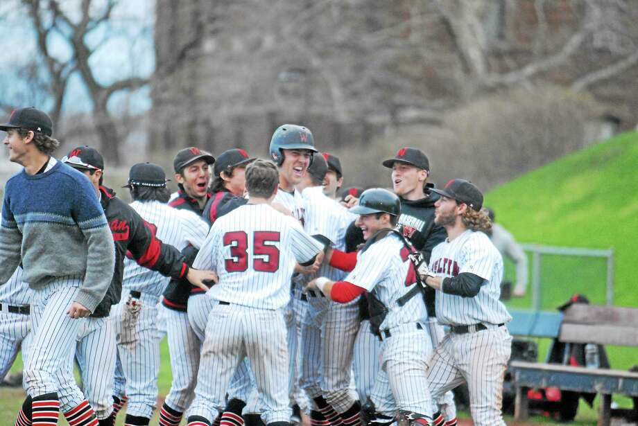 Wesleyan junior Sam Goodwin-Boyd is mobbed after scoring the winning run in the bottom of the ninth against Amherst. Photo: Jimmy Zanor — Middletown Press
