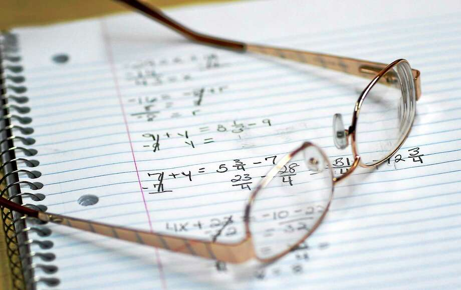 A student's glasses sitting on a notebook containing math exercises. Photo: AP Photo/Patrick Semansky  / AP