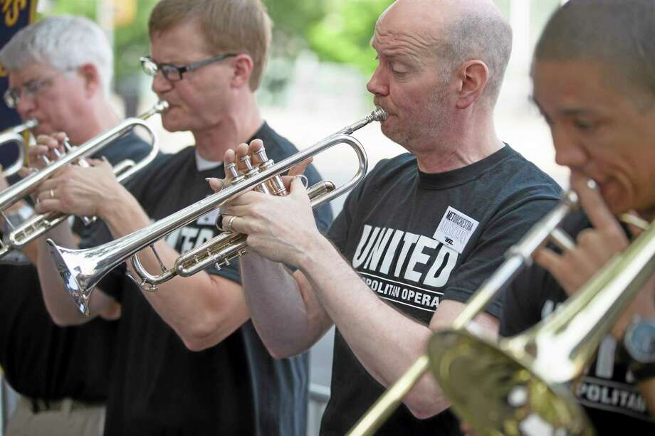 Demonstrators play their musical instruments outside Lincoln Center during a protest over a labor dispute with New York's Metropolitan Opera Friday in New York. Photo: John Minchillo — The Associated Press  / FR170537 AP