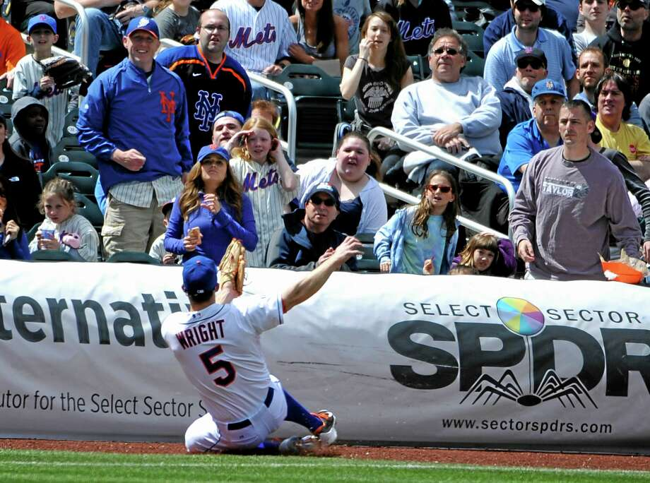 Fans watch New York Mets third baseman David Wright catch a foul ball in the fourth inning at Citi Field on Sunday. Photo: Kathy Kmonicek — The Associated Press  / FR170189 AP