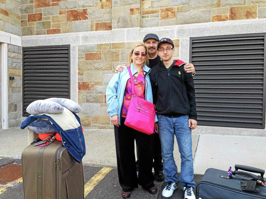 Adua Genovese, Mario Genovese and son Andrew Carducci prepare to leave on their trip to Italy which includes Mario Genovese's hometown of Melilli. Photo: Kaitlyn Schroyer — The Middletown Press