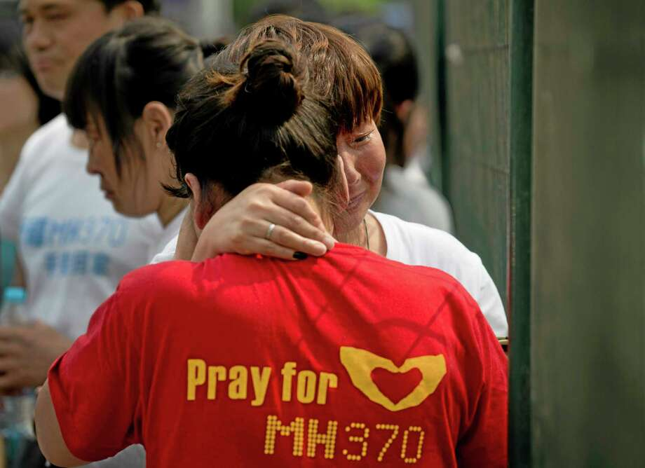 Chinese women, relatives of Chinese passengers onboard the Malaysia Airlines MH370 cry as they wait for Malaysia embassy staff to meet them outside the Malaysia embassy in Beijing, China Friday, April 25, 2014. About 50 relatives of Chinese passengers on the plane continued a sit-in protest outside the Malaysian Embassy after officials failed to show up to update them on the search. (AP Photo/Andy Wong) Photo: AP / AP