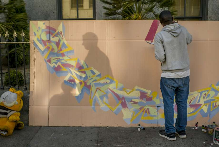 Jaz Cameron paints on a giant piece of found cardboard near Fifth and Mission streets in San Francisco. Photo: Santiago Mejia, The Chronicle