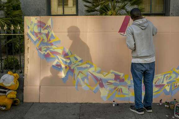 Jaz Cameron paints on cardboard near 5th and Mission streets on Wednesday, July 19, 2017, in San Francisco, Calif.