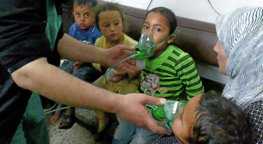 In this image taken from video obtained from the Shaam News Network, posted on April 16, 2014, an anti-Bashar Assad activist group, which has been authenticated based on its contents and other AP reporting, children are seen receiving oxygen in Kfar Zeita, a rebel-held village in Hama province some 200 kilometers (125 miles) north of Damascus. Syrian opposition activists and other witnesses tell The Associated Press that Syrian government forces have attacked rebel-held areas with poisonous chlorine gas in recent months. They say the attacks left scores of men, women and children coughing, choking and gasping for breath. The reports have been denied by the Syrian government and have yet to be confirmed by any foreign country or international organization. But if true, they highlight the limitations of the global effort to rid Syria of its chemical weapons. (AP Photo/Shaam News Network) Photo: AP / Shaam News Network