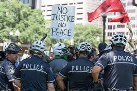 "A San Antonio police officer allegedly said ""F--- you, f----t"" to a man during a confrontation at the Travis Park Confederate statue removal in September. The officer was suspended without pay for three day.      Click ahead to view photos of protesters squaring off in Travis Park over the controversial statue."
