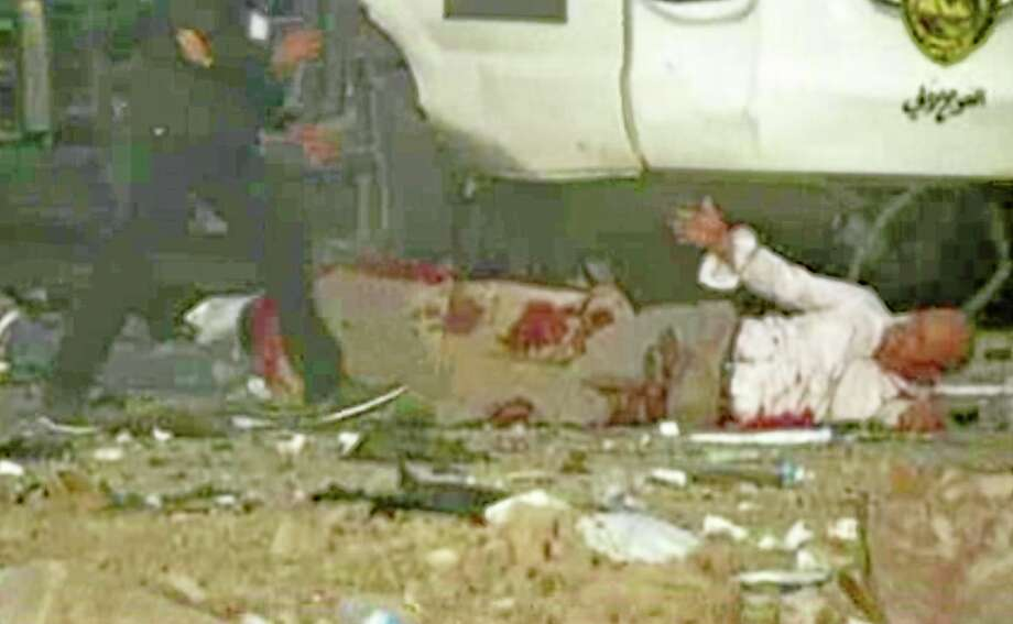 This image made from video shows a wounded man reaching out for help after a series of bombs that exploded Friday, April 25, 2014 at a campaign rally for a Shiite group in  Baghdad, Iraq, ahead of the country's parliamentary election. The blasts killed and wounded dozens, officials said. (AP Photo via AP video) Photo: AP / AP Video