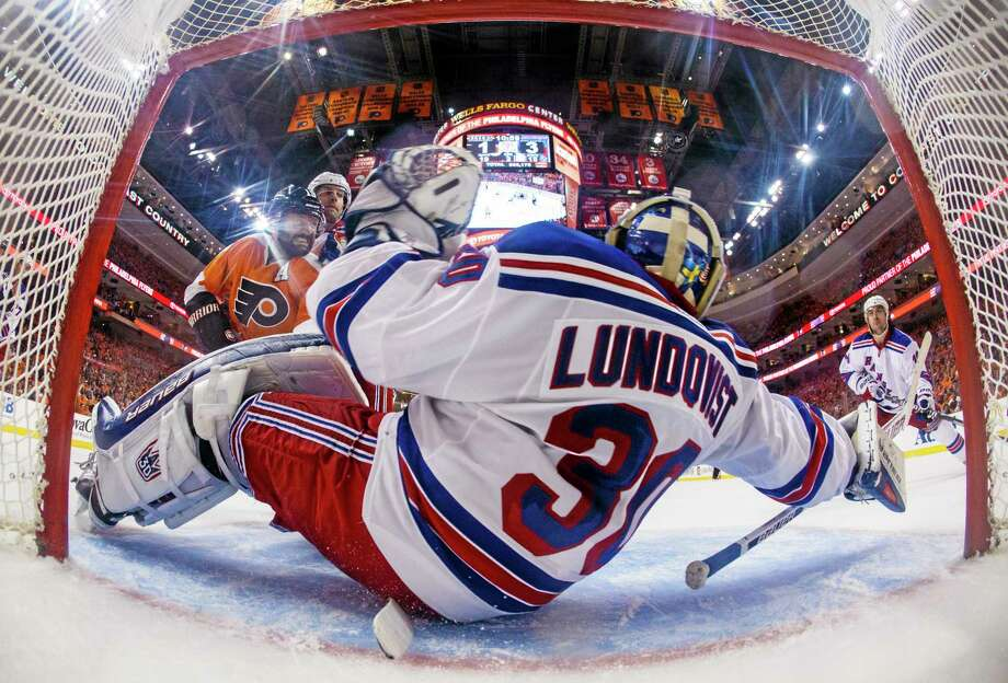 In this photo taken with a fisheye lens, New York Rangers goalie Henrik Lundqvist stops a shot against the Flyers in the second period of Game 3 on Tuesday in Philadelphia. Photo: Chris Szagola — The Associated Press  / FR170982 AP