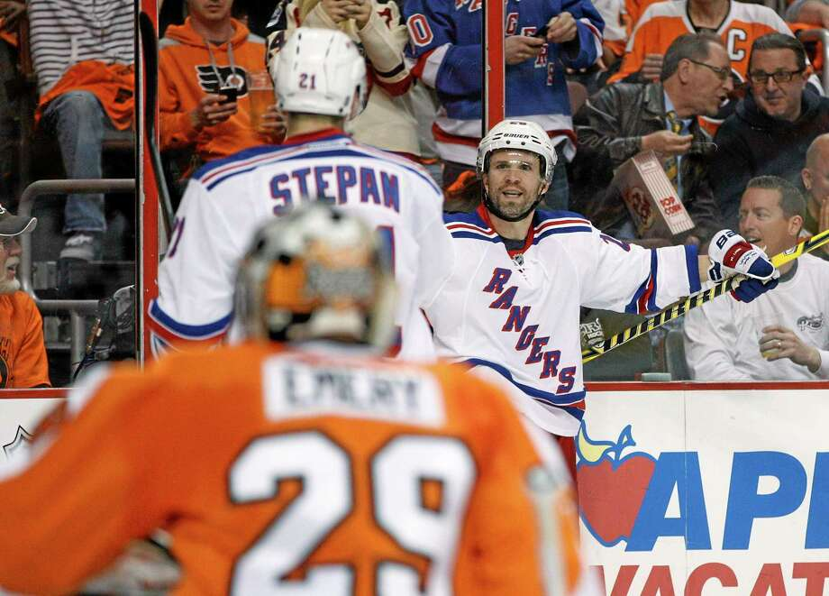 The Rangers' Martin St. Louis and Derek Stepan celebrate a goal as Flyers goalie Ray Emery watches during the first period of Game 3 on Tuesday in Philadelphia. Photo: Chris Szagola — The Associated Press  / FR170982 AP