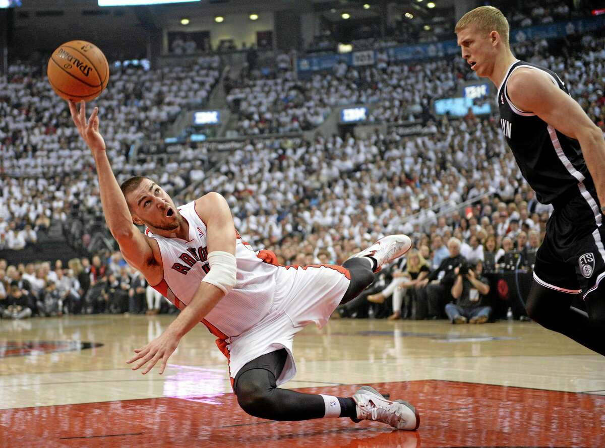 Toronto Raptors forward Jonas Valanciunas shoots while falling in front of the Brooklyn Nets' Mason Plumlee during the first half of Tuesday's game in Toronto.