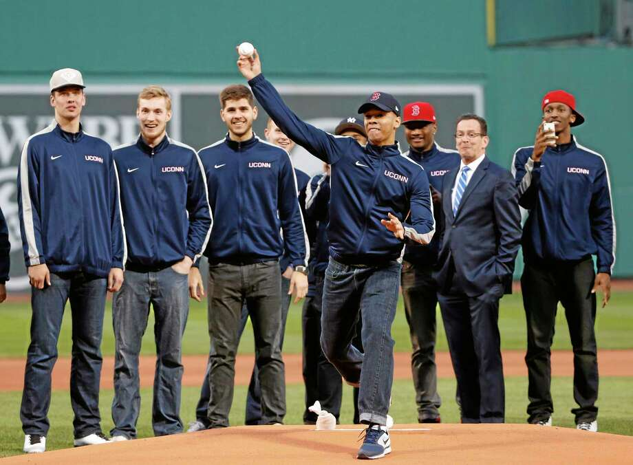 UConn men's basketball team members watch teammate Shabazz Napier throw a ceremonial first pitch prior to Tuesday's game between the Boston Red Sox and the New York Yankees at Fenway Park in Boston on Tuesday. At second from right is Connecticut Gov. Dannel P. Malloy. Photo: Elise Amendola  — The Associated Press  / AP