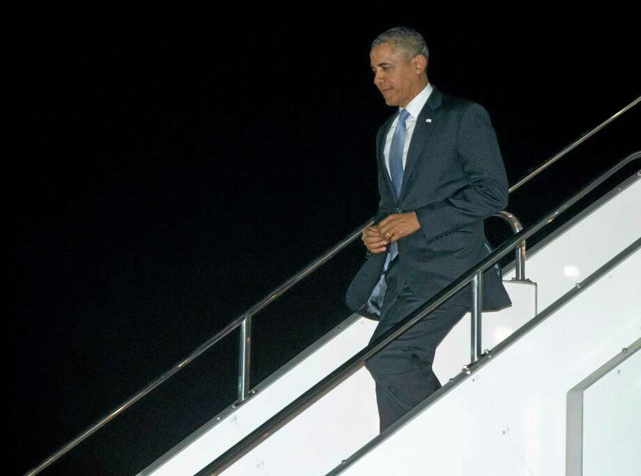U.S. President Barack Obama steps from Air Force One as he arrives at Haneda International Airport in Tokyo, Wednesday, April 23, 2014, as he begins a four-country trip through the Asia-Pacific region. (AP Photo/Carolyn Kaster) Photo: AP / AP