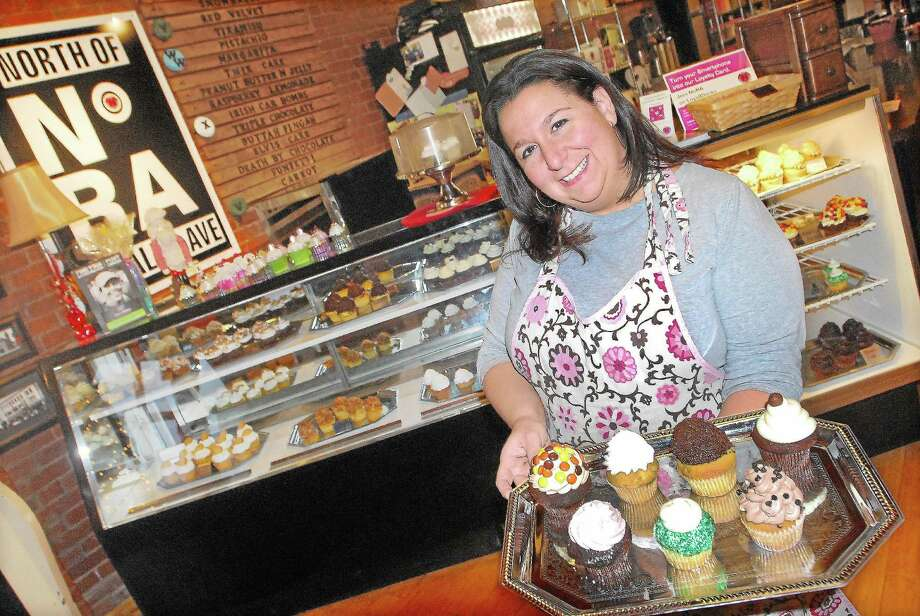 Carrie Carella, owner of NoRA Cupcake Company on Main Street in Middletown, displays a couple of favorites such as the Irish Car Bomb, Adult Twinkie and the Funky Monkey in this Middletown Press file photo. Photo: Catherine Avalone — The Middletown Press