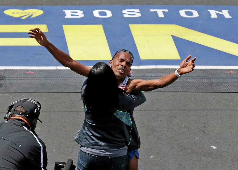 Meb Keflezighi, of San Diego, Calif., is hugged after crossing the finish line to win the 118th Boston Marathon Monday, April 21, 2014 in Boston. (AP Photo/Charles Krupa) Photo: AP / AP