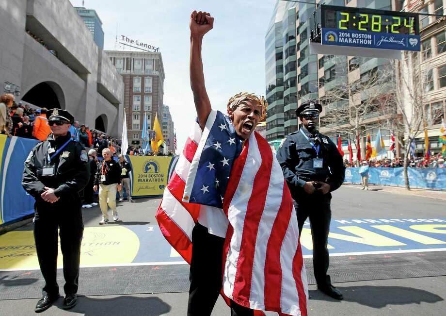 Meb Keflezighi, of San Diego, Calif., celebrates his victory in the 118th Boston Marathon, Monday, April 21, 2014, in Boston. (AP Photo/Elise Amendola) Photo: AP / AP