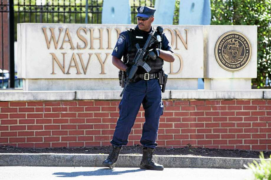 An armed officer who said he is with the Department of Defense, works near the gate at the Washington Navy Yard, closed to all but essential personnel, in Washington, on Tuesday, Sept. 17, 2013, the day after a gunman launched an attack inside the Washington Navy Yard on Monday, spraying gunfire on office workers in the cafeteria and in the hallways at the heavily secured military installation in the heart of the nation's capital. (AP Photo/Jacquelyn Martin) Photo: AP / AP