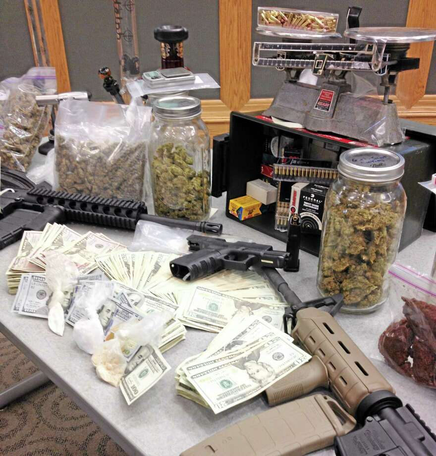 Stacks of cash and semi-automatic weapons are displayed on a table with suspected drugs and dealing equipment during a news conference on Monday, April 21, 2014 in, Ardmore, Pa. Montgomery County allege the leaders of a drug ring operation are 25-year-old Neil Scott and 18-year-old Timothy Brooks, both graduates of The Haverford School. (AP Photo/Kathy Matheson) Photo: AP / AP