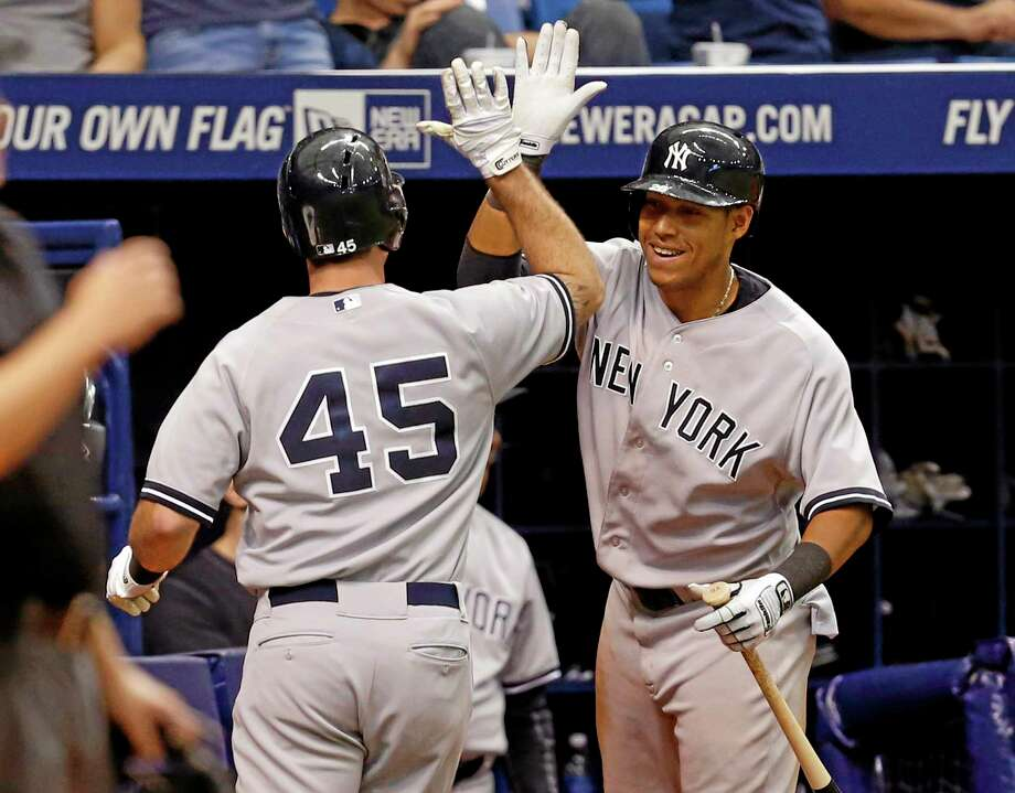 New York Yankees' Dean Anna (45) is congratulated by teammate Yangervis Solarte after scoring during the 12th inning of a baseball game against the Tampa Bay Rays, Sunday, April 20, 2014, in St. Petersburg, Fla. The Yankees won 5-1. (AP Photo/Mike Carlson) Photo: AP / FR155492 AP