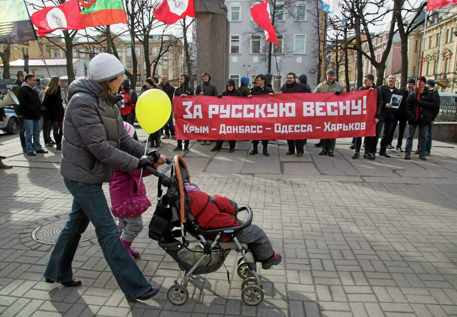 "A woman pushes a pram in front of activists of the Other Russia opposition group rallying in support of Russian people in Ukraine, in St. Petersburg, Russia, Saturday, April 5, 2014. Several dozen demonstrators gathered for a rally, held a banner reading ""For Russian Spring! Crimea, Donbas, Odessa, Kharkov,"" and their party flags. (AP Photo/Dmitry Lovetsky) Photo: AP / AP"