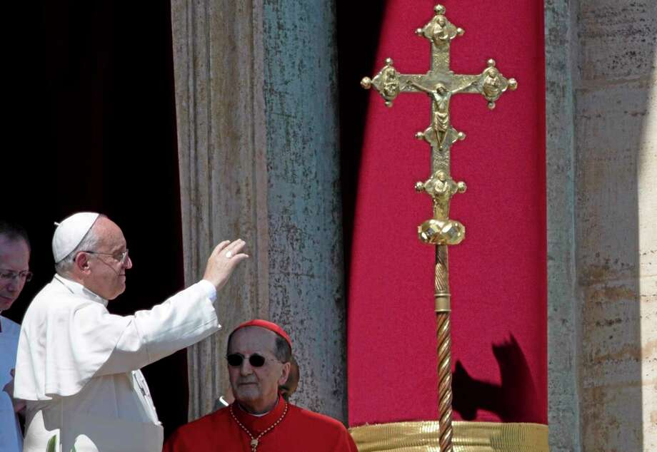 Pope Francis waves at the end of the Urbi and Orbi (Latin for to the city and to the world) blessing from the balcony of St. Peter's Basilica at the end of the Easter Mass in St. Peter's Square at the the Vatican Sunday, April 20, 2014. (AP Photo/Andrew Medichini) Photo: AP / AP