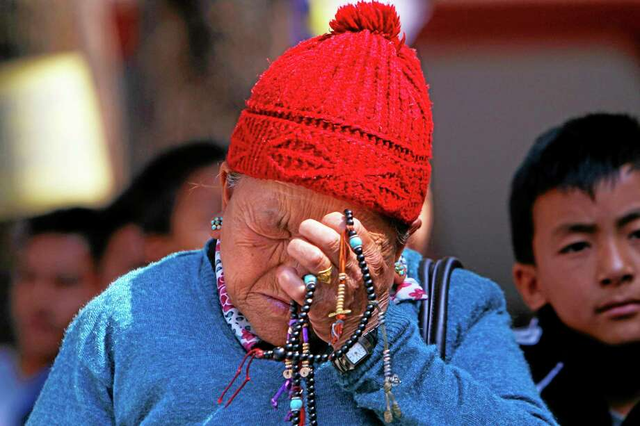 Mother of Nepalese mountaineer Ang Kaji Sherpa, killed in an avalanche on Mount Everest, holds prayers beads in her hand and cries while she waits for his body Saturday at Sherpa Monastery in Katmandu, Nepal. Photo: Associated Press  / AP