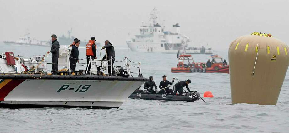 South Korean navy personnel install a buoy to mark the sunken passenger ship Sewol in the water off the southern coast near Jindo, South Korea, Friday. Rescuers scrambled to find hundreds of ferry passengers still missing Friday and feared dead, as fresh questions emerged about whether quicker action by the captain of the doomed ship could have saved lives. Photo: Associated Press  / Yonhap