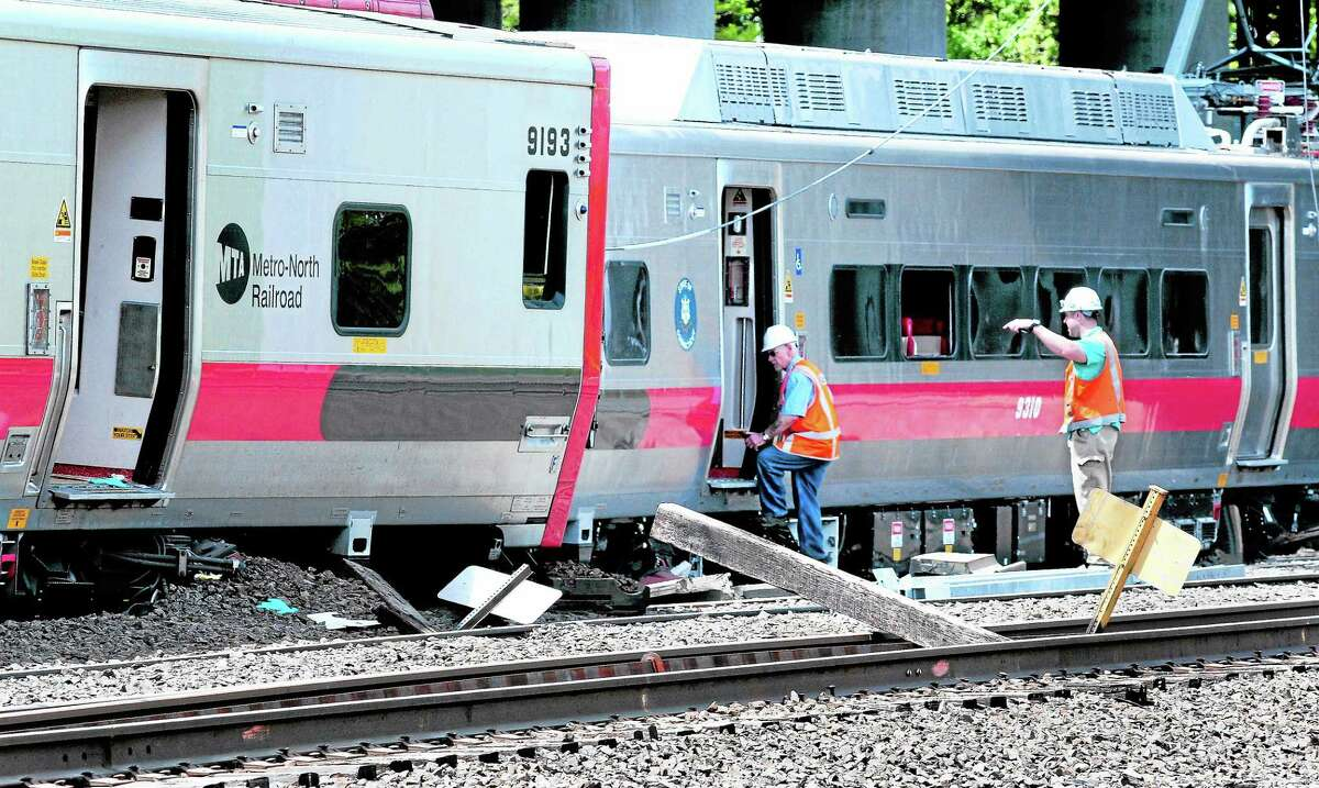 Investigators enter the northbound Metro North train involved in a derailment in Bridgeport near the Fairfield line on 5/18/2013. At left is the southbound train involved in the accident. ¬ Photo by Arnold Gold/New Haven Register