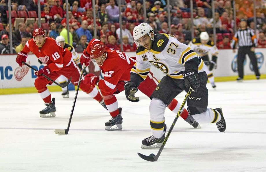 Boston Bruins forward Patrice Bergeron (37) skates with the puck while pursued by Detroit Red Wings defenseman Kyle Quincey (27) and forward Joakim Andersson (63) during the first period in Detroit on April 2. Photo: Tony Ding — The Associated Press  / FR143848 AP