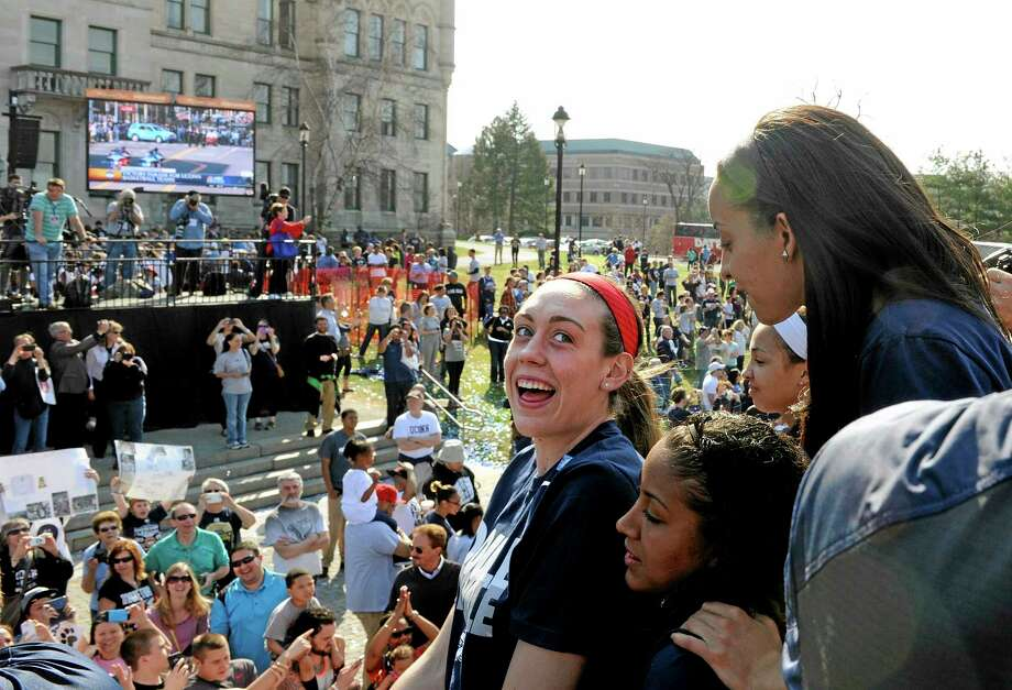 Sophomore Breanna Stewart, center, looks back at Bria Hartley, top right, and Kaleena Mosqueda-Lewis during the UConn dual parade on Sunday in Hartford. Photo: Fred Beckham — The Associated Press  / FR153656 AP